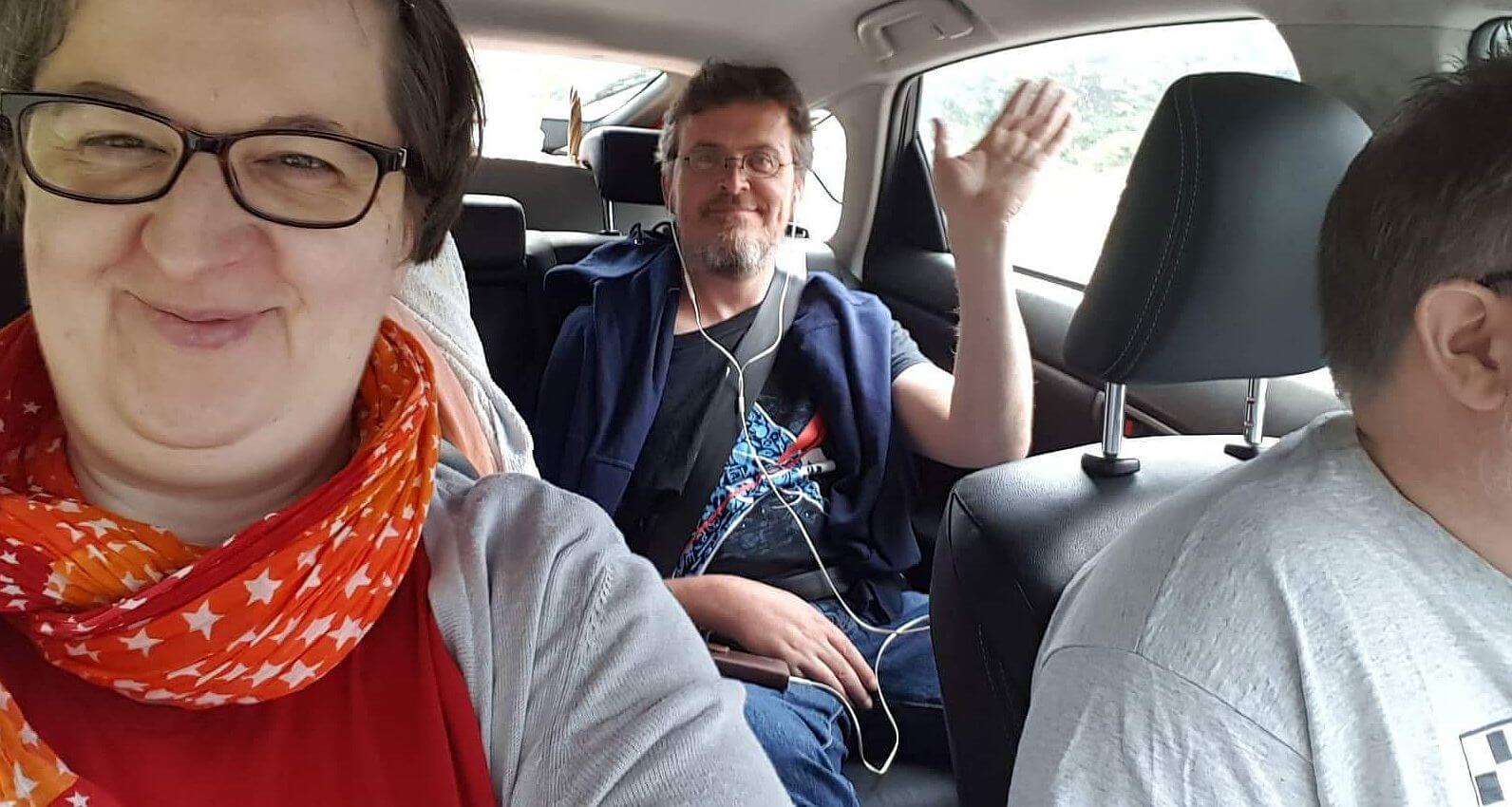 Kai winkt vom Rücksitz im Auto